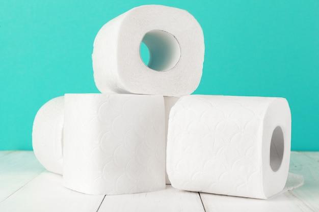 Рулоны туалетной бумаги на бирюзовом ярком фоне
