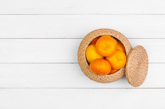 白い木製の表面、上面に柑橘系の果物のボウル