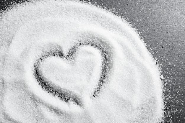 Рассеянный сахар на черном фоне крупным планом