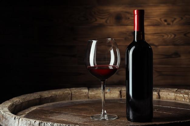 ボトルと暗い背景の木で撮影した木製の樽に赤ワインのグラス