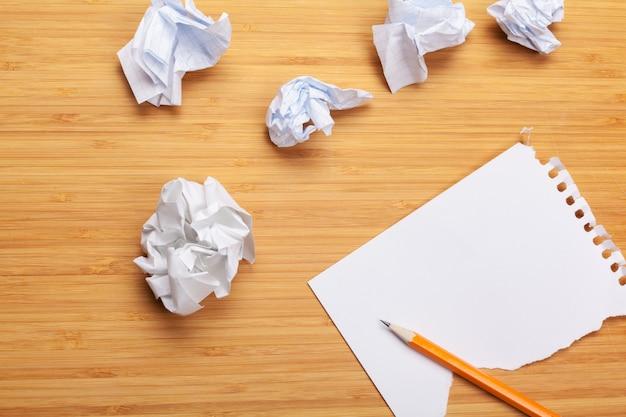 木製のテーブルに白いメモ帳。メモ帳の周りには、しわくちゃの紙がたくさんあります
