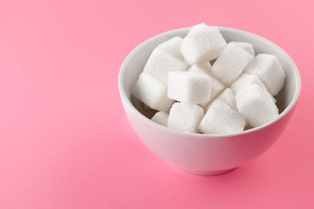 ピンクの背景の上にボウルに砂糖キューブ