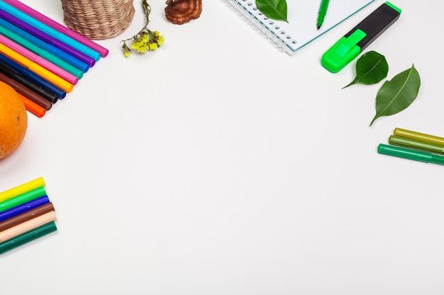 白い紙の上の紙とカラフルなフェルトペン