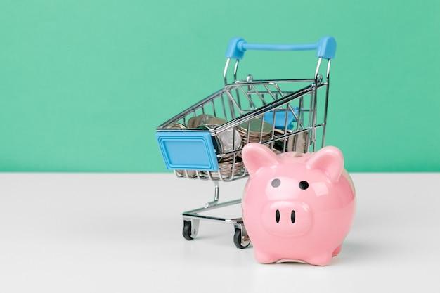 ショッピングカートとピンクの貯金箱