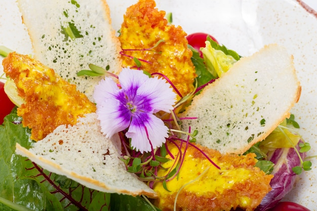 Салат с курицей на белой тарелке на светлом фоне