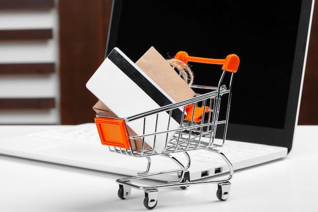 オンラインショッピングの概念。ショッピングカート、机の上のノートパソコン
