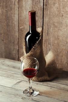 ガラスと木製のテーブルに対してテーブルに美味しい赤ワインの瓶