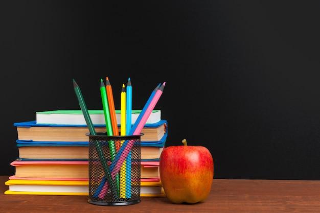 学校のコンセプトに戻る。本と木製の机の上のリンゴと黒板