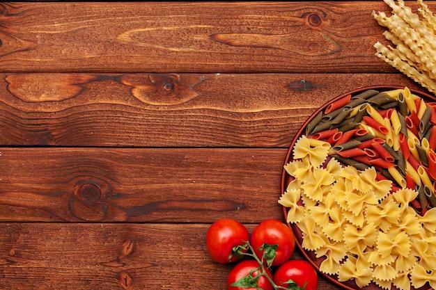 パスタとコピースペースを持つ木製の背景の食材。上面図。