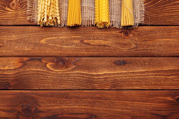 Сушеные макароны на деревянном фоне