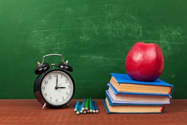 机の上の本、紙、鉛筆の山に赤いリンゴ