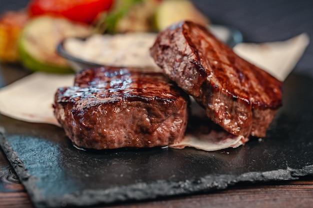 灰色のスレートに野菜と牛肉のグリルステーキ