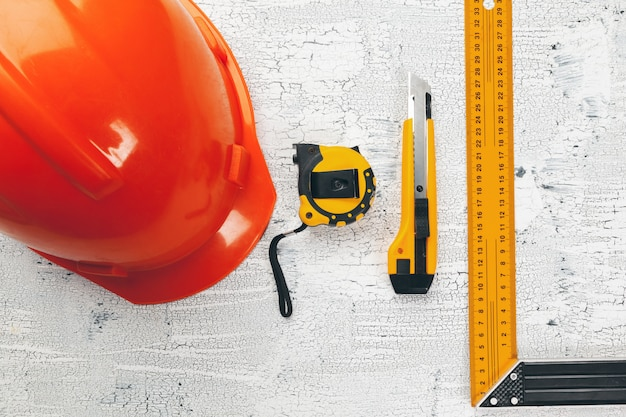 建築設計図と設計図ロール、および作業台上の描画器具。