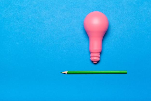 独創的なアイデアのコンセプト。ピンクの電球と鉛筆のトップビュー