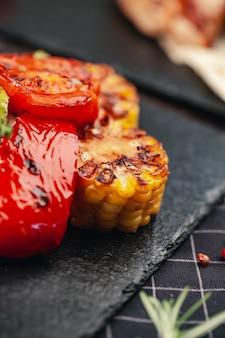 Закрыть вверх на гриле на деревянные помидоры и кукуруза