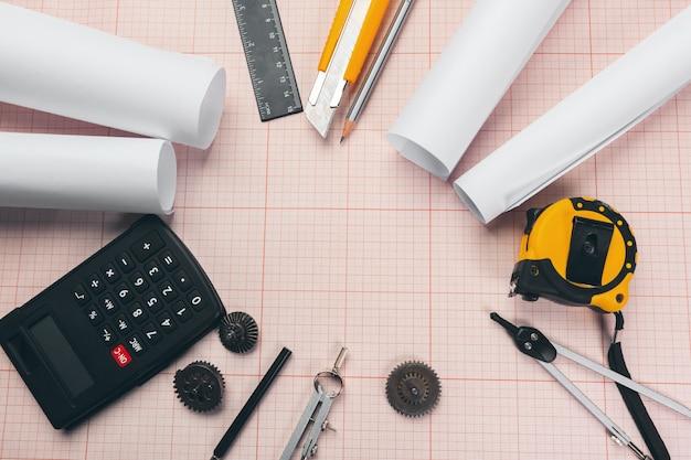 Инструменты рисования на красном фоне миллиметровки с копией пространства