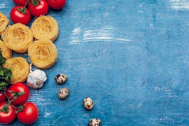 青色の背景にさまざまなパスタ。料理のコンセプト。上面図