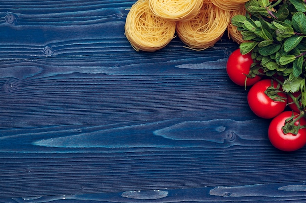 木製の青い背景にタリアテッレイタリアパスタの平面図クローズアップ詳細