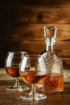 コニャックまたは素朴なテーブルの上のグラスにウイスキー