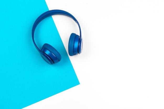 Синие наушники на синем и белом цвете