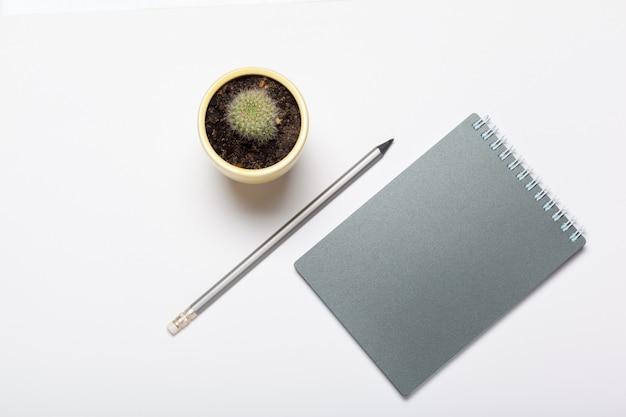 Серый блокнот и карандаш на рабочем столе вид сверху