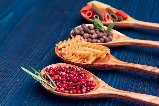 パスタスパゲッティ、野菜、スパイス、木製のテーブルの上