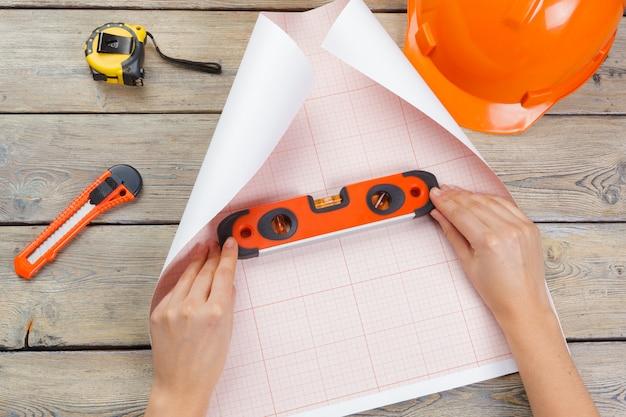 進行中の建築プロジェクト。エンジニアリングの概念。建築家の手トップビュー