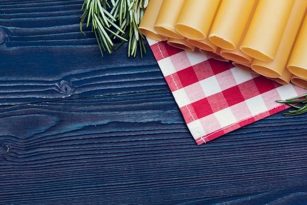 暗い青い木製のテーブル、上面の背景にイタリアの生パスタ