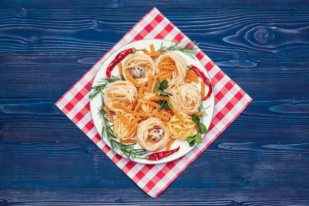 暗い青い木製のテーブル、トップビューでイタリアの生パスタ