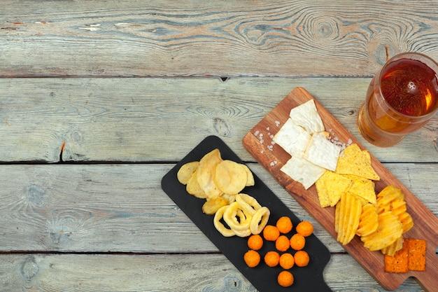 ラガービールと木製の表面テーブルのスナック。