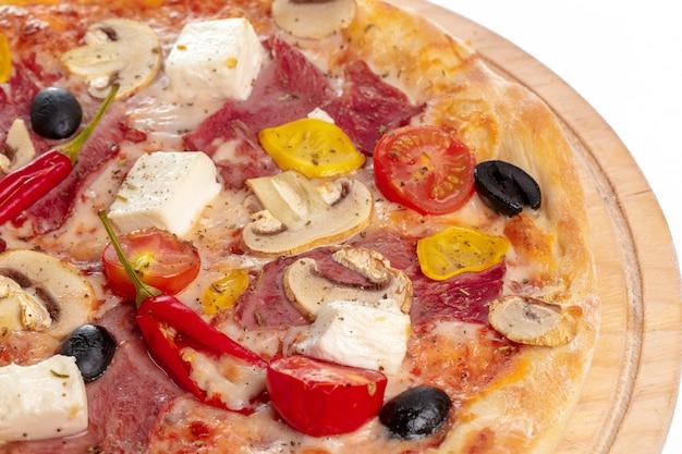 木製の表面にスライスして提供するおいしいホットピザ