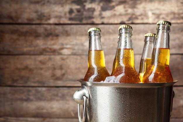 Холодные бутылки пива в ведре на деревянной поверхности