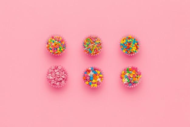 Различные сахарные брызги на розовом фоне