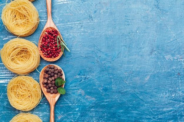 パスタスパゲッティ、野菜、スパイス、木製の背景に