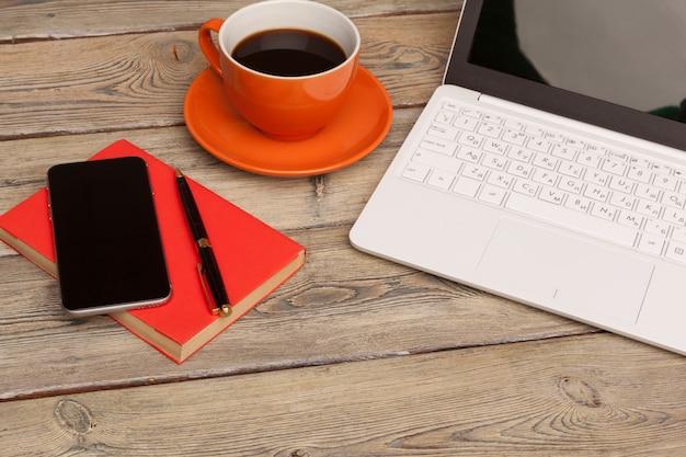 木製のテーブルのオレンジ色のプレートにコーヒーカップ。オフィスインテリア