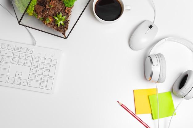 コンピューターのキーボードと消耗品のモダンな白いオフィスデスクテーブル。コピースペースを持つ平面図、フラットレイアウト。