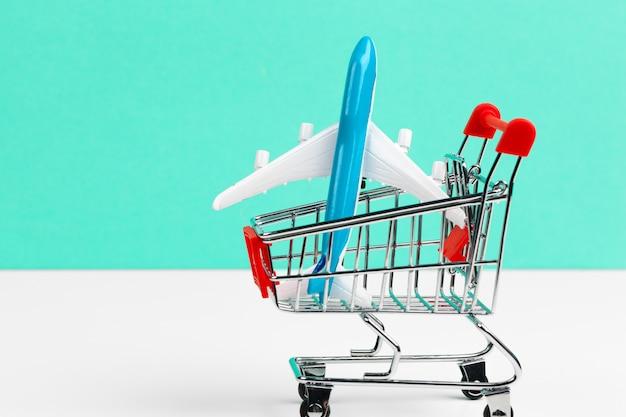 白いテーブルにおもちゃの飛行機でショッピングトロリーをクローズアップ