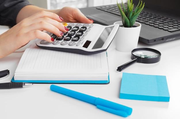 Бизнес женщина, работающая с рукой финансовых данных, используя калькулятор