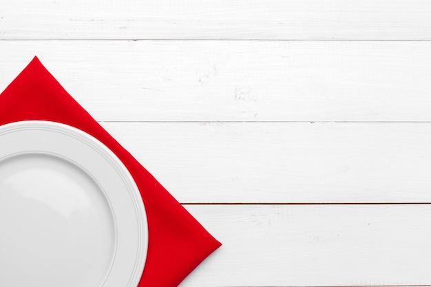 空の皿と木製のテーブルの上のタオル