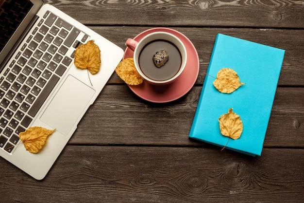 空白のノートブックとラップトップのオフィステーブル/コーヒーカップ