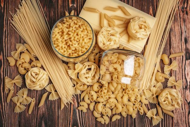 Различные виды итальянской пасты деревенском фоне