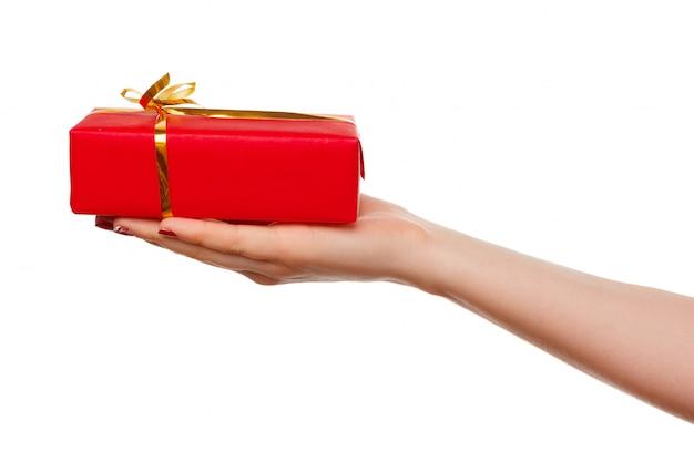 Рука держа малую красную коробку с лентой в своей ладони изолированной на белизне.