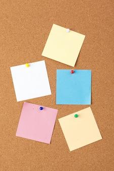 ピン付きのいくつかのカラフルな空白ノートとコルクボード