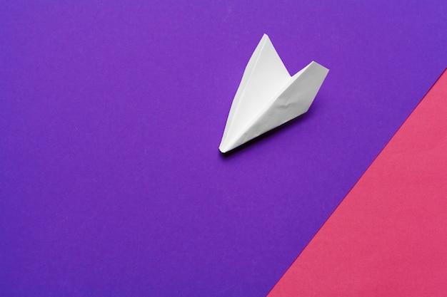 カラフルな紙の上の白い紙飛行機