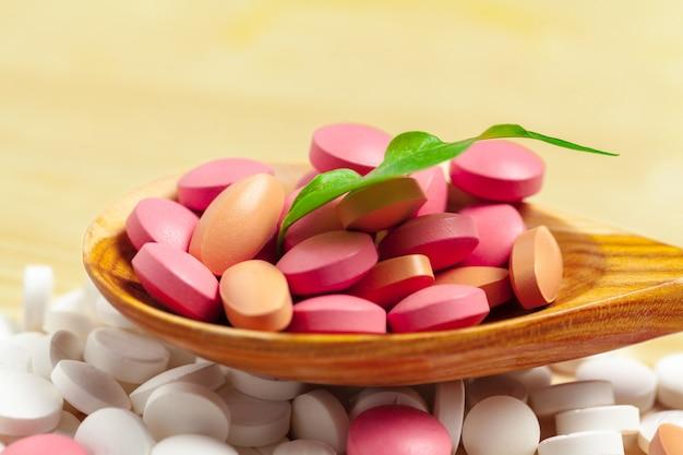 薬のカプセル、木のスプーンの丸薬