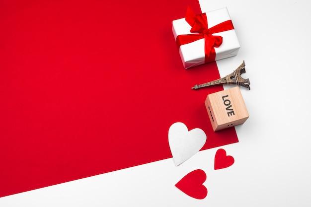 赤の背景にチョコレートの心のマグカップ。フラットレイアウト構成。ロマンチックな聖バレンタインの日のコンセプト