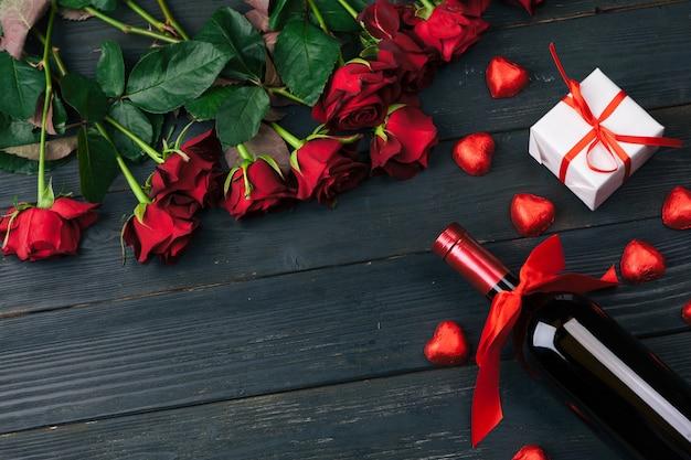 バレンタインの日グリーティングカード。木製のテーブルに赤いバラの花、ワイン、ギフトボックス。