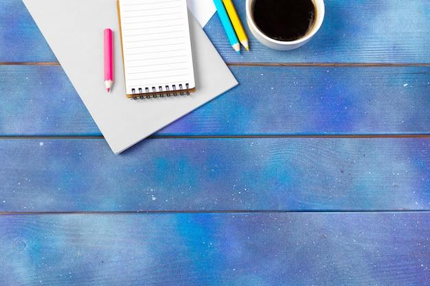 青い木製の背景にコーヒーカップと空のメモ用紙。オフィス、作家、研究コンセプト