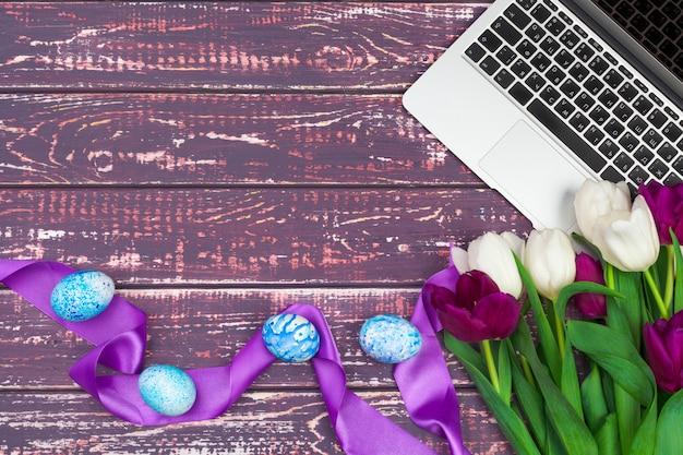 イースターエッグ、ラップトップ、木製の背景にチューリップの花束