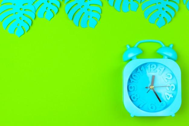 背景色の目覚まし時計と熱帯の葉
